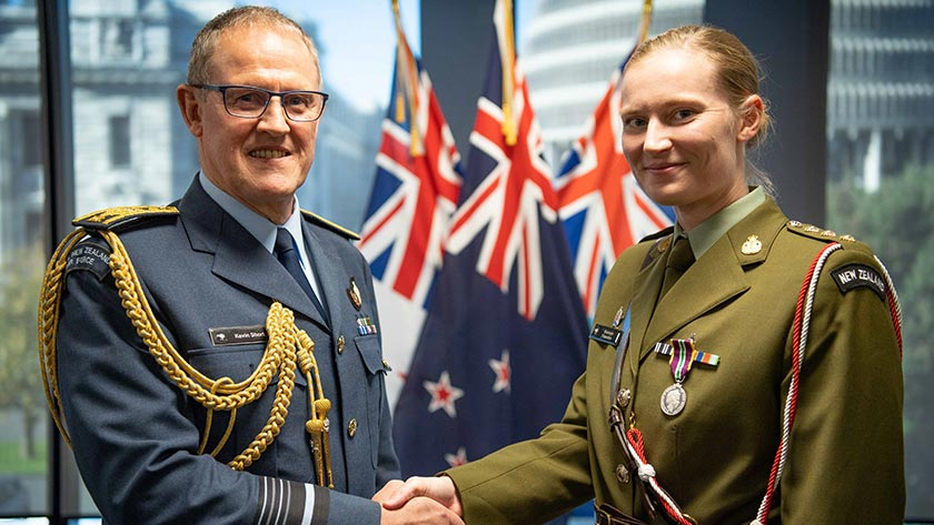 Chief of Defence Force Air Marshall Kevin Short presents Captain Bronwyn Flewellen with her meritorious service medal.