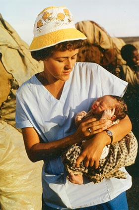 Barbara Walker holding a baby, her first delivery, in Las Dhure Camp, Somalia