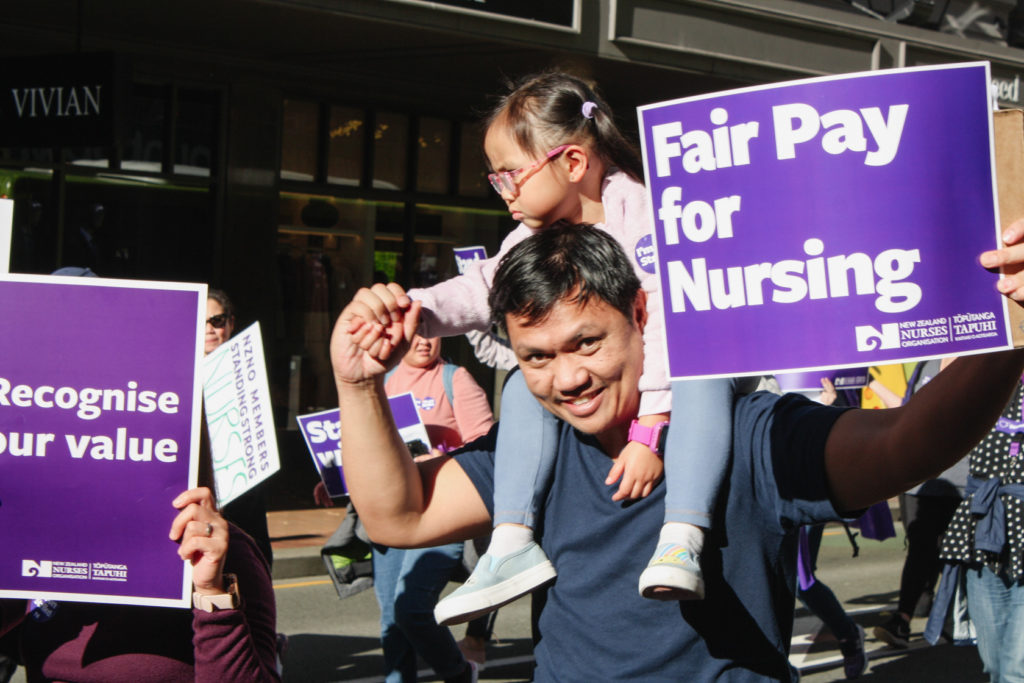 Dad and daughter holding a 'Fair pay for Nursing' sign