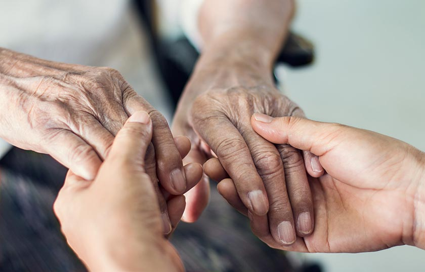 The hands of an old woman being held in the hands of a young woman. PHOTO: ADOBE STOCK.