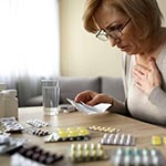Senior lady feeling unwell, puzzling over various medications.