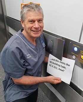 """Health and safety representative Ben Basevi in a lift, holding a sign that says """"...and this meets the NZ Building Code, D2.3.1(c)...how?"""""""