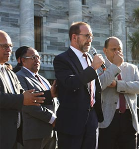 Health Minister Andrew Little flanked by government MPs while speaking to NZNO DHB members.