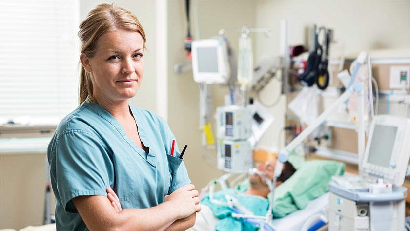 Portrait of confident nurse standing arms crossed with patient resting in background at hospital. PHOTO: ADOBE STOCK
