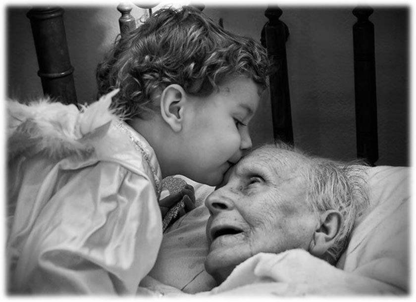 Small child kissing their aged bedridden grandparent on the forehead