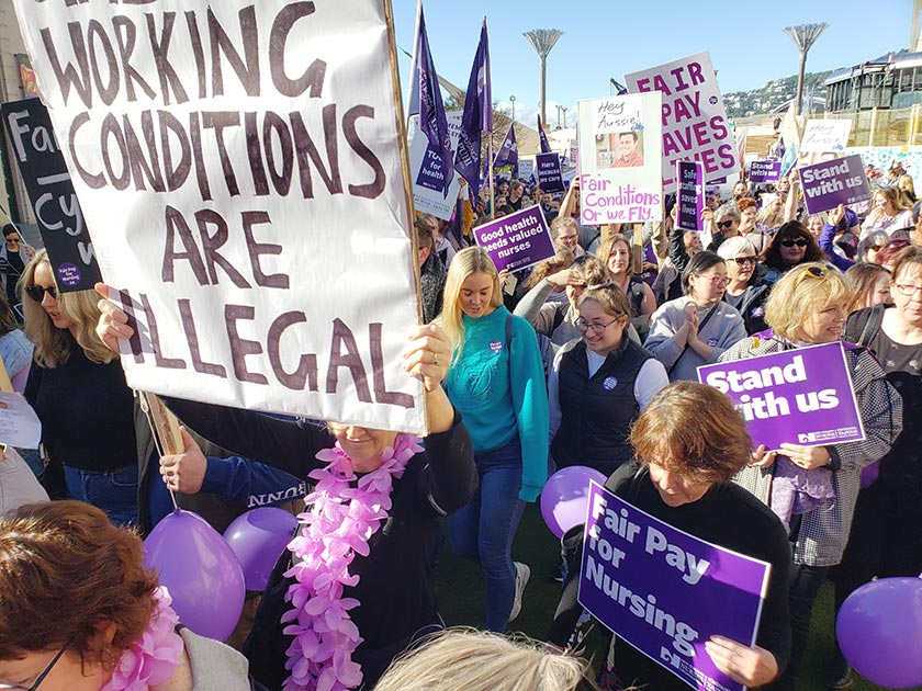 Striking nurses at a demonstation with a banner reading 'Working conditions are illegal'.